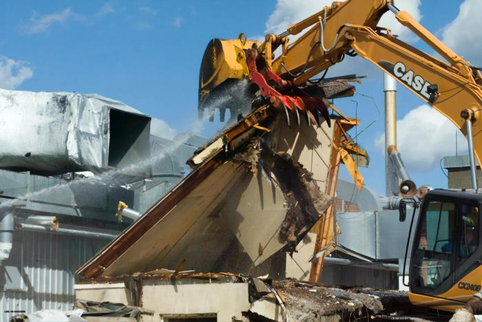 Image of a yellow digger tearing a wall down. There is debris, and the wall is about to fall over. It's set against a blue cloudy sky.