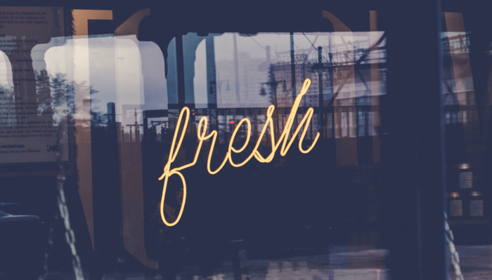 Image of a yellow neon sign in a window saying the word Fresh