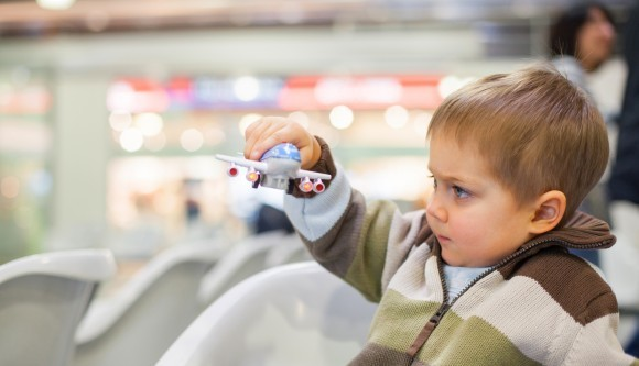 Boy-playing-with-toy-airplane-in-airport-web-580x333.jpg