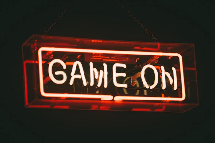 Image of a red and pink neon sign saying Game On, against a black background. The words are a surrounded by a neon square boxing them in